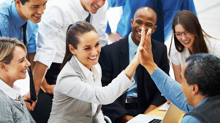 Beautiful business woman high fiving colleague during meeting